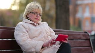 Senior woman sits on the bench near the road and uses red cell phone. Woman looking and flipping through the photos in her cell phone