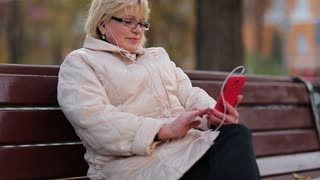 Senior woman sits on the bench near the road and uses red cell phone. Woman looks and flips through the photos in her smartphone. Female with smartphone. Businesswoman with mobile phone