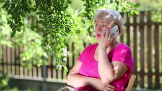 Senior woman sits on the chair in garden and talks on the mobile phone. Blonde woman speaks on cell phone. Female with white smartphone. Businesswoman with smartphone sits under tree in garden