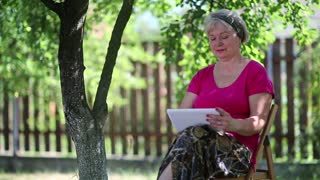 Senior woman sits on the chair in garden and uses white tablet computer. Businesswoman with tablet pc sits under tree in garden. Female with tablet computer