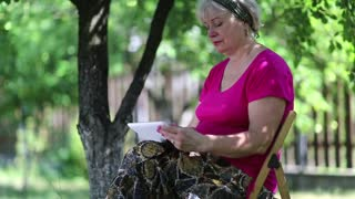 Senior woman sits on the chair in garden and uses white tablet computer. Female with tablet computer. Businesswoman with tablet pc sits under tree in garden