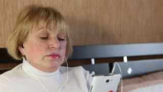 Senior woman with closed eyes with smartphone sits on the sofa and listens to music