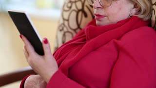 Senior woman with eyeglasses sits on a sofa and reads electronic book. Female reads a book. Blonde woman with e-book