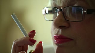 Senior woman with glasses smoking a cigarette. Female smoker, close up shot