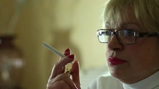 Senior woman with glasses smoking a cigarette, female smoker, close up shot
