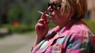 Senior woman with glasses smoking a cigarette. Female smoker