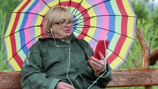 Senior woman with many-coloured umbrella sits on the swing bench and communicates via red smartphone