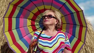 Senior woman with many-coloured umbrella stands near hayrick. Female with umbrella. Blonde woman in sun glasses with many-coloured umbrella stands near haystack and looks into the distance