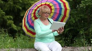 Senior woman with umbrella sits on a fallen tree in the forest and uses tablet computer. Woman with tablet PC