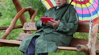 Senior woman with umbrella sits on the swing bench and uses red smartphone. Woman looks at the screen of his smartphone. Female with smartphone. Businesswoman with mobile phone