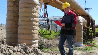 Service engineer at heat electropower station. Worker in yellow hard hat near heating main pipeline. Engineering supervision