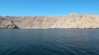 Ship sails along Musandam peninsula, Sultanate of Oman, Gulf of Oman. Oman - arab country in southeastern coast of the Arabian Peninsula. Musandam - governorate of Oman, located on Musandam peninsula