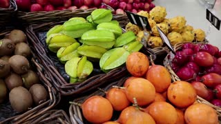 Shop counter with fresh exotic fruits. Fresh exotic fruits in supermarket. Green carambola fruits, kiwi and other exotic fruits