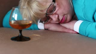 Sleeping woman lying on a sofa with a glass of cognac