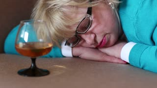Sleeping woman lying on the sofa with a glass of cognac