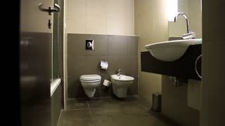 Slider shot of interior of small bathroom. Toilet facility