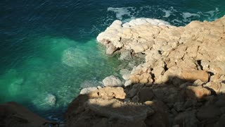 Stony coast of Dead Sea in Hashemite Kingdom of Jordan. Green water and white salt deposits on yellow stones