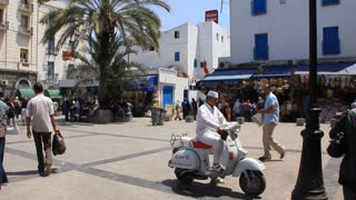Street in Tunis, Tunisia. Man riding a scooter