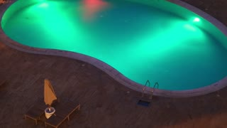 Swimming pool with night illumination that change colors. Outdoor hotel pool with cold water