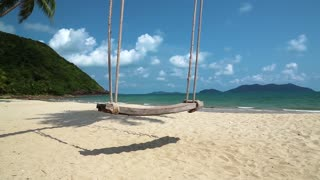 Swing on the shore of a beautiful island. Video with stereo sound