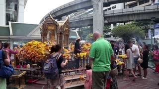 THAILAND, BANGKOK, APRIL 11, 2014: Thai people near mini buddhist temple in Bangkok downtown, Thailand