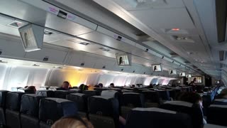THAILAND, BANGKOK, MARCH 30, 2014: People watching a movie aboard an airplane