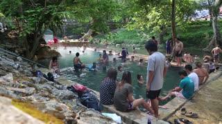 THAILAND, KANCHANABURI PROVINCE, APRIL 5, 2014: People in radon pool in Kanchanaburi Province, western Thailand.