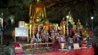 THAILAND, KANCHANABURI PROVINCE, KWAI RIVER, APRIL 1, 2014: People and Golden Buddha statue inside temple in the cave