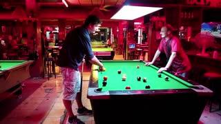 THAILAND, PATTAYA, MARCH 31, 2014: Men playing billiards inside big billiards club at Walking street in Pattaya, Thailand