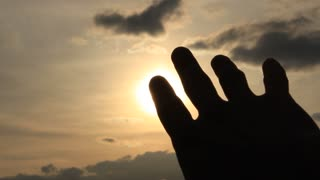 The hand catches sun in a fist