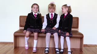 Three girls sitting on a bench in the school