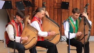 Three men in national costume playing bandura (Ukrainian string instrument)