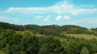 Timelapse of clouds and beautiful green hills with coniferous trees. Video without birds and defects