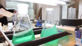 Two flasks with green fluid in chemical-analysis laboratory