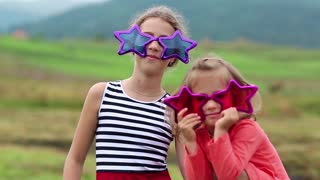 Two funny girls in pink and purple glasses looks at the camera. Cheerful girls in big glasses in the shape of stars looks at the camera