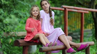 Two girls sits on a wooden bench and embrace. Sisters sits together, communicates and embrace