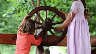 Two girls turn wooden wheel together. Sisters turn wooden wheel and embrace