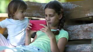 Two little girls with red smartphone sits on the swing bench. Two sisters with cell phone sits on the swing bench