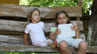 Two little girls with tablet computer sit on the swing bench. Two sisters with tablet PC sit on the swing bench