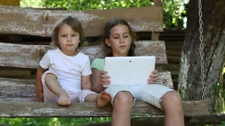 Two little girls with tablet computer sits on the swing bench. Two sisters with tablet PC sits on the swing bench
