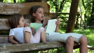 Two little girls with white tablet computer sits on the swing bench. Female with tablet computer. Children with Tablet PC. Two sisters with tablet PC sits on the swing bench in garden