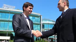 Two men in business suits shake hands
