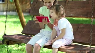 Two nice girls with red smartphone sits on the swing bench. Two sisters with cell phone sits on the swing bench. Female with smartphone