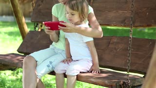 Two nice girls with red smartphone sits on the swing bench. Two sisters with cell phone sits on the swing bench