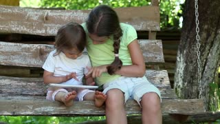 Two sisters with tablet PC sits on the swing bench. Two little girls with tablet computer sits on the swing bench