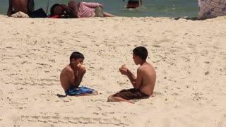 Two Tunisian boys eat on the beach