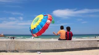 Two Tunisian boys look on many-coloured parachute near seashore in Sousse, Tunisia