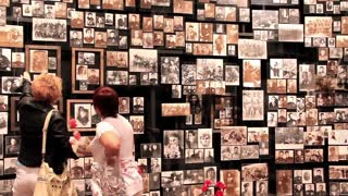 Two women by wall with old photos