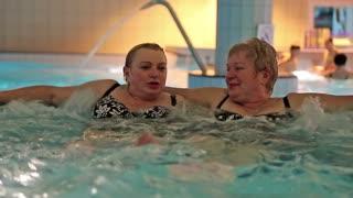 Two women in jacuzzi inside big water park