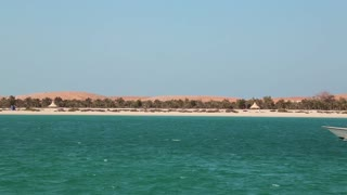 UAE, ABU DHABI, FEBRUARY 4, 2016: Motor boat floats near the Lulu island in Abu Dhabi. Artificial, man-made island. View from Corniche Road. Abu Dhabi - capital and second most populous city in UAE